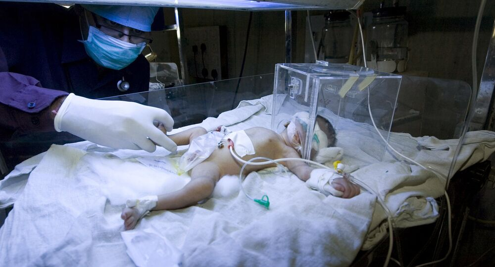 An Indian doctor attends to an unnamed child in The Pediatric Intensive Care Unit at The Civil Hospital in Ahmedabad on February 25, 2009