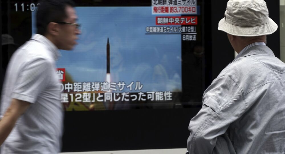A man, right, watches a public TV screen broadcasting news of North Korea's launch of missile, in Tokyo