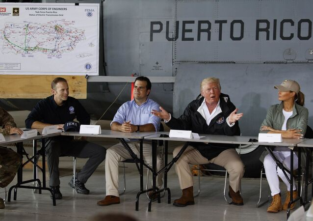 President Donald Trump and first lady Melania Trump participate in a briefing on hurricane recovery efforts with first responders at Luis Muniz Air National Guard Base, Tuesday, Oct. 3, 2017, in San Juan, Puerto Rico as Puerto Rico Gov. Ricardo Rosselló, left of the President, looks on.