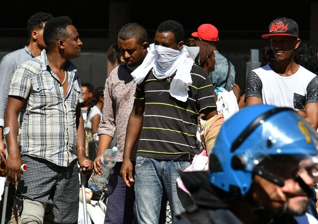 Refugees and asylum seekers wait after being displaced from a palace in the center of Rome on August 23, 2017