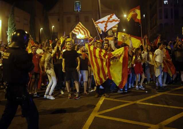Anti-independence demonstrators wave Spanish flags as they march in Barcelona, Spain, Tuesday Oct. 3, 2017