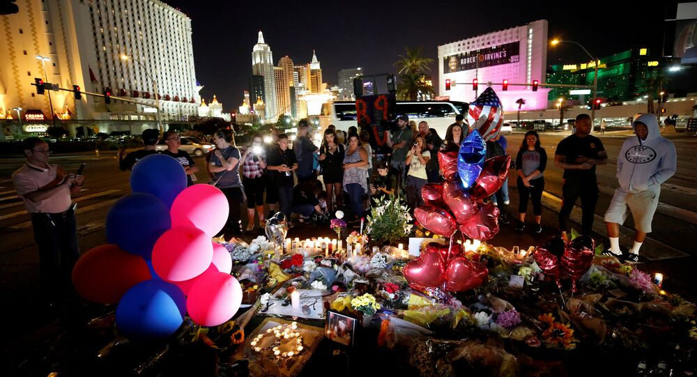 People gather at a makeshift memorial in the middle of Las Vegas Boulevard following the mass shooting in Las Vegas, Nevada, U.S., October 4, 2017
