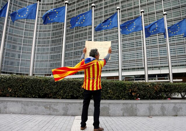 Catalan Raimon Castellvi, wearing a flag with an Estelada (Catalan separatist flag), holds a sign as he protests outside the European Commission in Brussels after Sunday's independence referendum in Catalonia, Belgium October 2, 2017