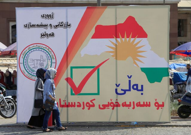 Iraqi women walk on the street, near banners supporting the referendum for independence for Kurdistan in Erbil, Iraq September 21, 2017