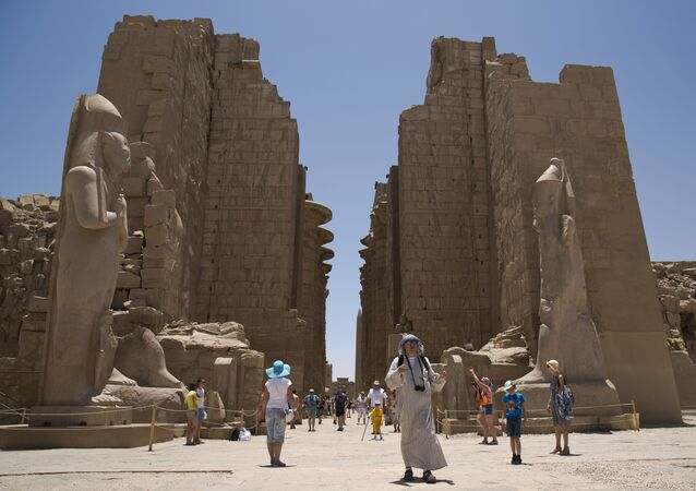 A Russian tourist, center, wears Bedouin traditional dress as he visits the ruins of the Karnak Temple in Luxor, Egypt, Thursday, June 11, 2015