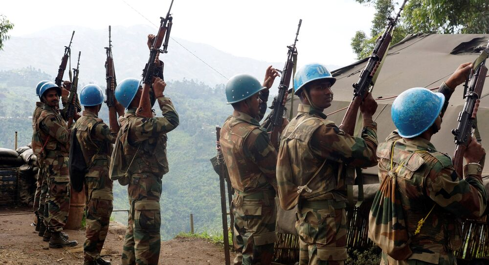 Indian soldiers, serving in the U.N. peacekeeping mission in Congo (MONUSCO), hold up their weapons at their base after patrolling the villages in Masisi, 88 km (55 miles) northwest of Goma, Congo on October 4, 2013