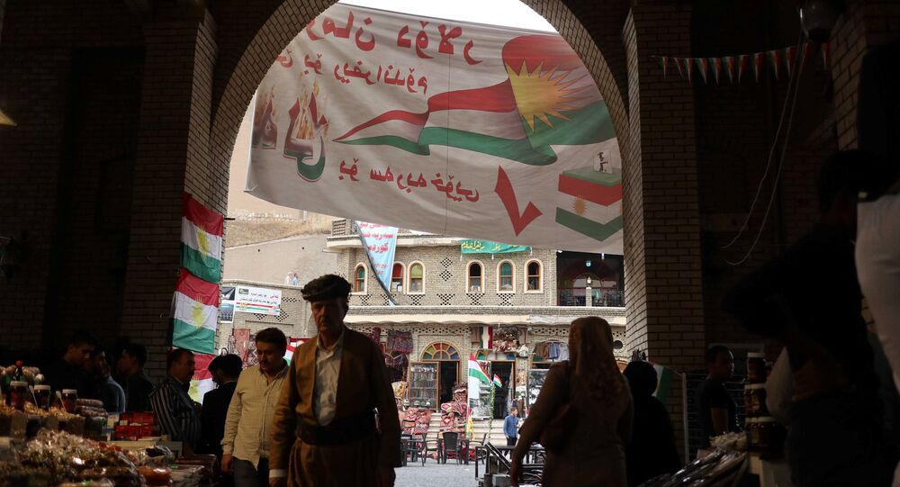 People walk inside old city market of Erbil near banners supporting the referendum for independence for Kurdistan in Erbil, Iraq