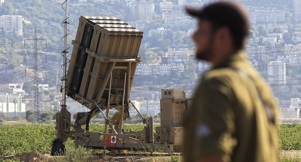An Israeli soldier is seen next to an Iron Dome rocket interceptor battery deployed near the northern Israeli city of Haifa, Wednesday, Aug. 28, 2013.