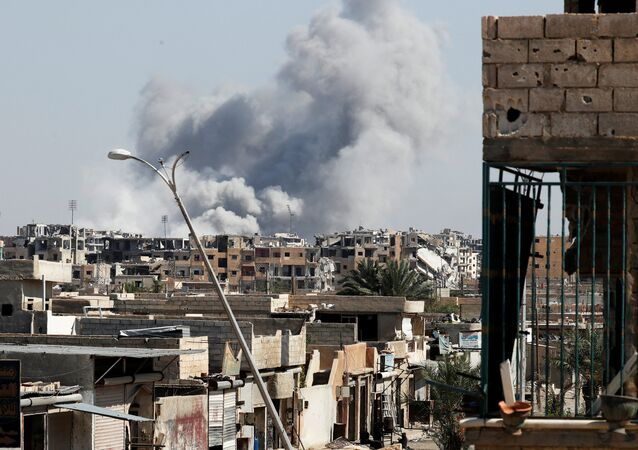 Smoke rises near the stadium where the Islamic State militants are holed up after an air strike by coalition forces at the frontline, in Raqqa, Syria October 12, 2017