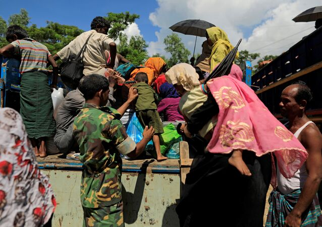 A military member helps a Rohingya refugee boy who arrived from Myanmar to get onto a truck that will take him to a refugee camp from a relief centre in Teknaf, near Cox's Bazar in Bangladesh, October 13, 2017
