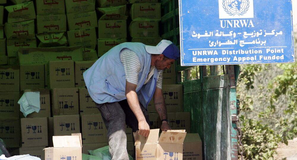 A Palestinian worker unloads boxes as provisions are by the United Nations Relief and Works Agency for Palestine Refugees in the Near East (UNRWA). (File)