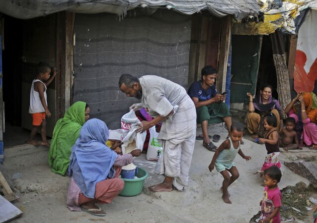 In this Tuesday, Sept. 12, 2017 photo, a Rohingya refugee distributes wheat, donated by locals, among other refugees at a camp for the refugees in New Delhi, India
