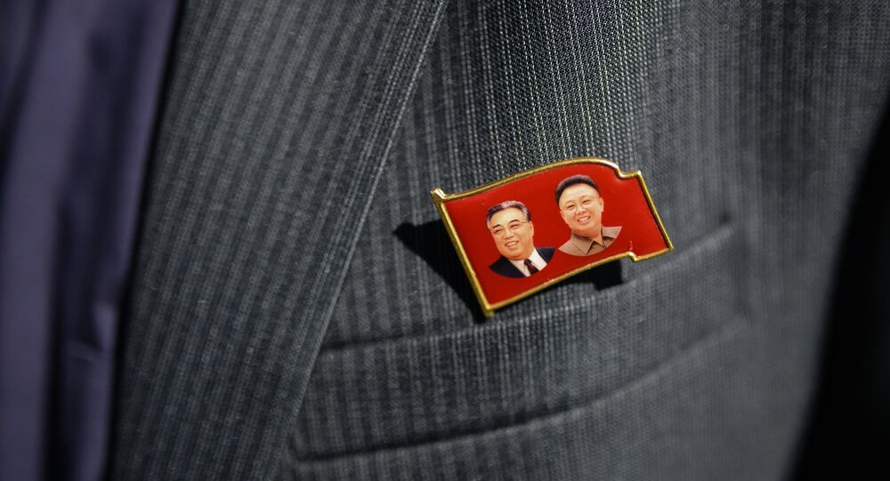 Badge with portraits of Kim Il Sung and Kim Jong Il on the blazer of a member of the delegation of the Democratic People's Republic of Korea (DPRK)