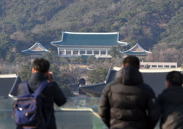 (File) People look at the presidential Blue House (C) in Seoul on March 10, 2017
