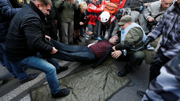 An injured man receives help during a rally by supporters of former Georgian President Mikheil Saakashvili and different political parties demanding an electoral reform, in front of Ukrainian parliament in Kiev, Ukraine October 17, 2017 - Sputnik International
