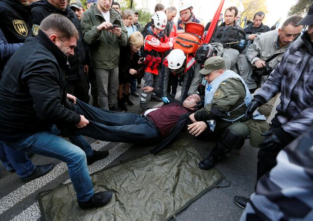 An injured man receives help during a rally by supporters of former Georgian President Mikheil Saakashvili and different political parties demanding an electoral reform, in front of Ukrainian parliament in Kiev, Ukraine October 17, 2017