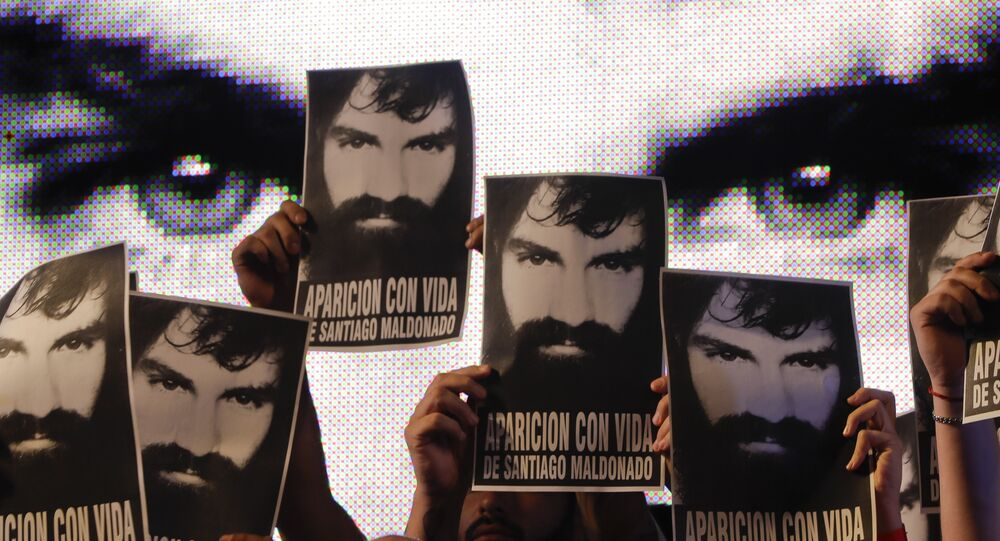In this Friday, Sept. 1, 2017 photo, demonstrators hold photos of missing activist Santiago Maldonado, during a protest at Plaza de Mayo in Buenos Aires, Argentina.