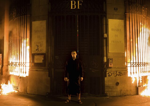 Russian artist Petr Pavlensky poses in front of a Banque de France building after setting fire to the window gates as part of a performance in Paris