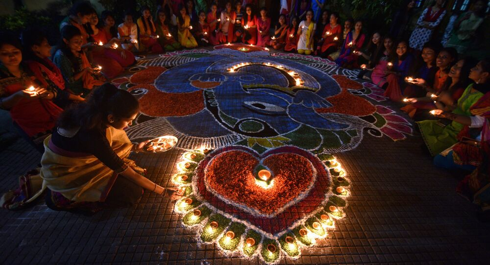 Students pose after lighting oil lamps around a Rangoli, a traditional pattern made from coloured powders and flower petals outside their hostel to celebrate Diwali, the Hindu festival of lights, in Guwahati, India, October 19, 2017