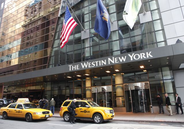 FILE - In this Wednesday, Feb. 1, 2012, file photo, a man hails a taxi in front of the Westin New York hotel, in New York.