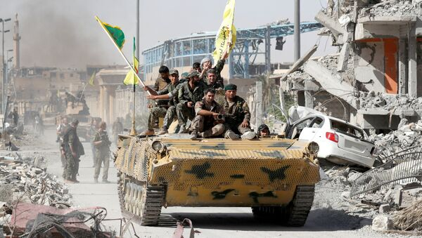 Syrian Democratic Forces (SDF) fighters ride atop of military vehicle as they celebrate victory in Raqqa, Syria, October 17, 2017 - Sputnik International