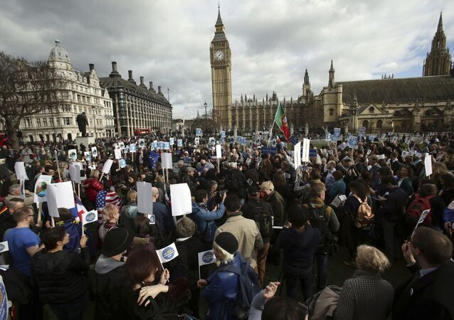 People gather in Parliament Square as part of a national day of action in support of migrants in the UK, in London with the Houses of Parliament back right, Monday Feb. 20, 2017. British lawmakers are set to hold a debate on Monday in London to consider a call for U.S. President Donald Trump to be denied an official state visit to the U.K., but the Conservative government insists the invitation remains firmly in place.