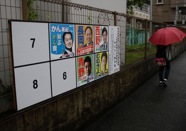 A woman walks in the rain past election posters as Typhoon Lan approaches Japan's mainland, in Osaka, western Japan, October 22, 2017