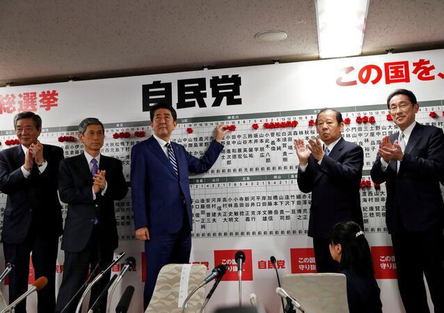 Japan's Prime Minister Shinzo Abe, leader of the Liberal Democratic Party (LDP), puts a rosette on the name of a candidate who is expected to win the lower house election, as his party's lawmakers applaud at the LDP headquarters in Tokyo, Japan October 22, 2017