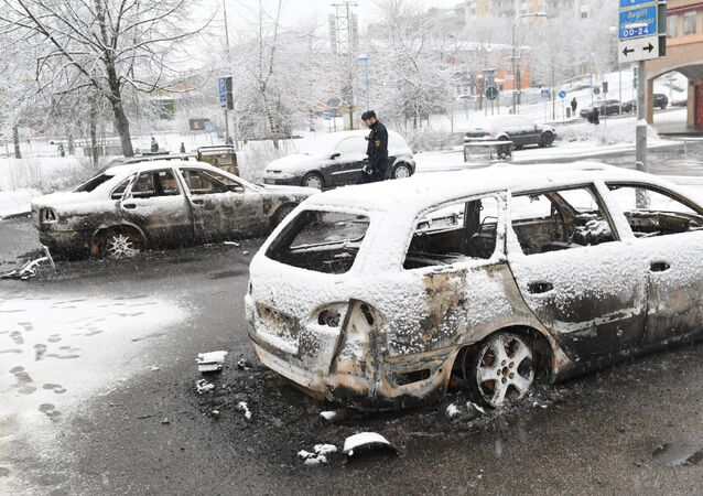 A policeman investigates a burned out car in the suburb Rinkeby, outside Stockholm, on February 21, 2017. Several cars was set in to fire after a riot in Rinkeby. The turmoil started when the police was going to arrest a man in the area