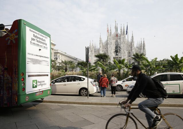 A poster advertising the upcoming referendum is placed on the back of a tourist bus riding past the Duomo gothic cathedral, in Milan, Italy, Wednesday, Oct. 11, 2017