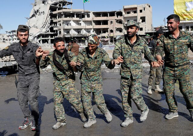 Fighters of Syrian Democratic Forces dance along a street in Raqqa, Syria October 18, 2017.