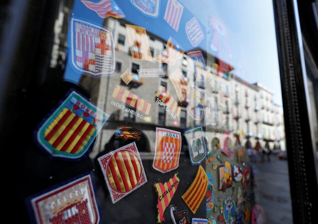Badges bearing regional flags are sen behind a window reflecting a square in Girona, Spain, October 7, 2017