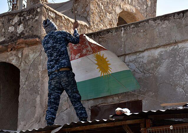 An Iraqi soldier removes a Kurdish flag from Altun Kupri on the outskirts of Irbil, Iraq, Friday Oct. 20, 2017