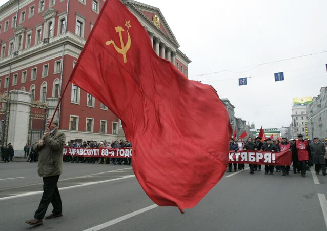 Communist supporter carries the red flag as others carry a banner declaring Long Live the 88th Anniversary of the October Revolution, during the rally to commemorate the Bolshevik Revolution, marking a long-sacred former holiday that was an official working day for the first time in decades in Moscow, Monday, Nov. 7, 2005.