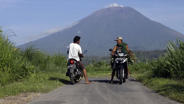 Villagers on their motorcycles talk each other with Mount Agung volcano in the background in Karangasem, Bali, Indonesia, Wednesday, Oct. 25, 2017 - Sputnik International