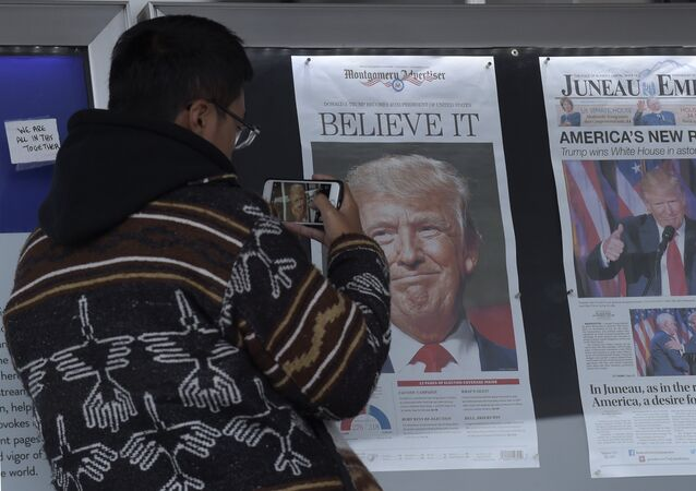 Zheng Gao of Shanghi, China, photographs the front pages of newspapers on display outside the Newseum in Washington, Wednesday, Nov., 9, 2016