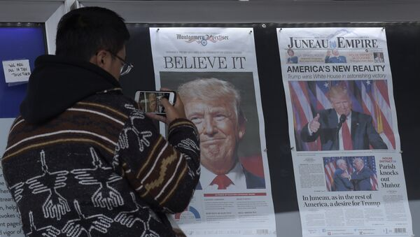 Zheng Gao of Shanghi, China, photographs the front pages of newspapers on display outside the Newseum in Washington, Wednesday, Nov., 9, 2016 - Sputnik International