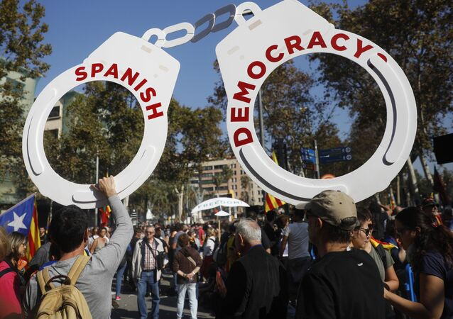 Protesters hold fake handcuffs as they take part a rally outside the Catalan parliament in Barcelona, Spain, Friday, Oct. 27, 2017.