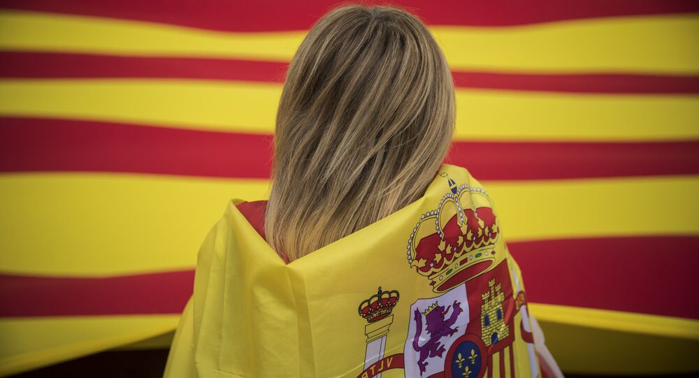 A woman wearing a Spanish flag on her shoulders looks at a giant flag of Catalonia as people celebrate a holiday known as Dia de la Hispanidad or Spain's National Day in Barcelona, Spain, Thursday, Oct. 12, 2017.