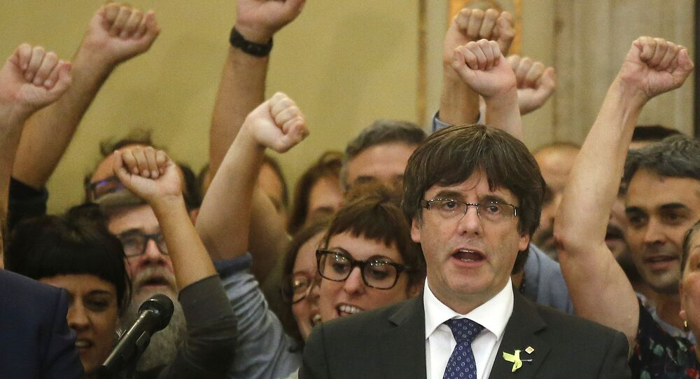 Carles Puigdemont sings the Catalan anthem inside the parliament after a vote on independence in Barcelona, Spain, Friday, Oct. 27, 2017.