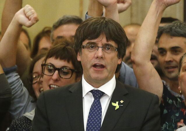 Catalan President Carles Puigdemont sings the Catalan anthem inside the parliament after a vote on independence in Barcelona, Spain, Friday, Oct. 27, 2017.