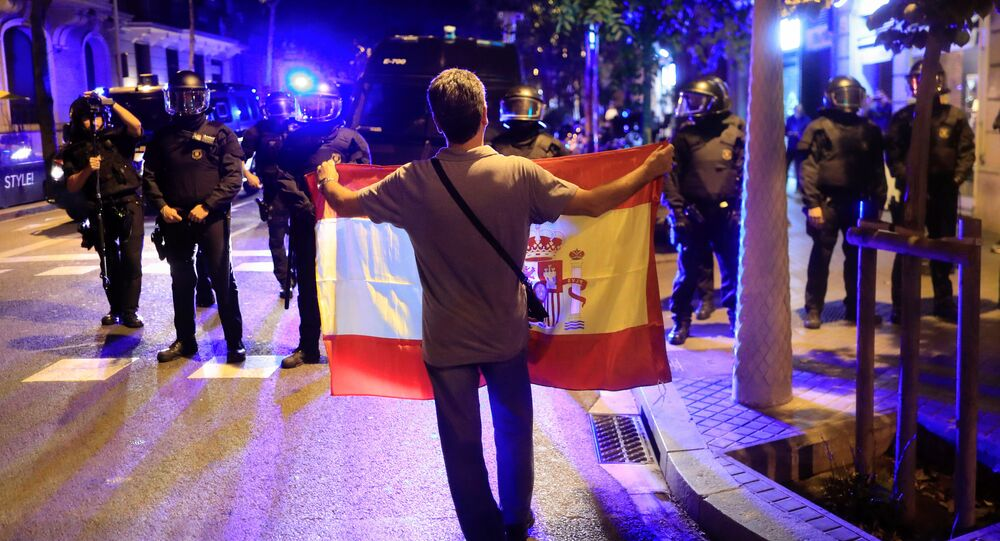 A pro unity demonstrator displays a Spanish flag to Catalan Regional Police officers during a protest after the Catalan regional parliament declared independence from Spain in Barcelona, Spain, October 27, 2017