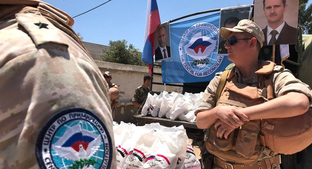 Servicemen of the Russian Center for Reconciliation of Opposing Sides in Syria hand out humanitarian aid in Jiba in the Quneitra province, Syria