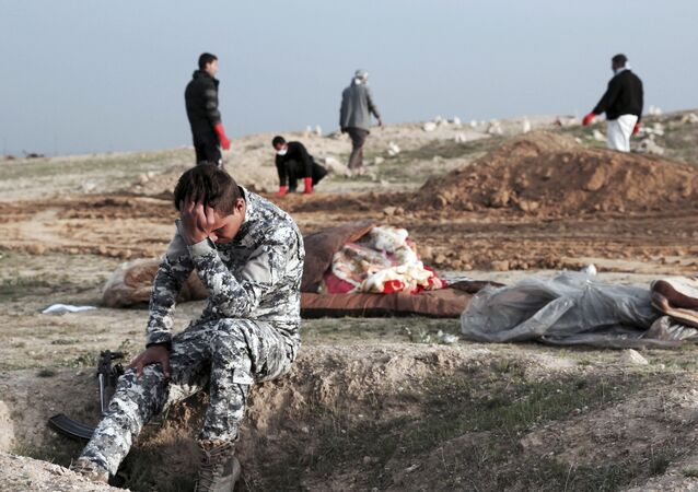 An Iraqi policeman collects himself at the burial site for bodies found in a mass grave containing some two dozen people, many of them children, in an area recently re-taken from Islamic State militants in Hamam al-Alil, Iraq, Wednesday, March 15, 2017