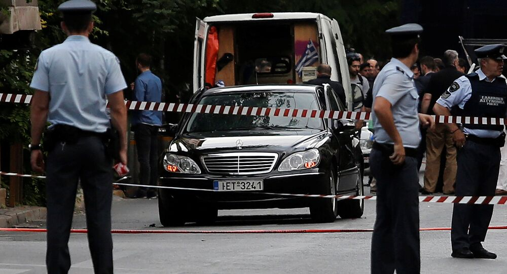 Police secure the area around the car of former Greek prime minister and former central bank chief Lucas Papademos following the detonation of an envelope injuring him and his driver, in Athens, Greece, May 25, 2017