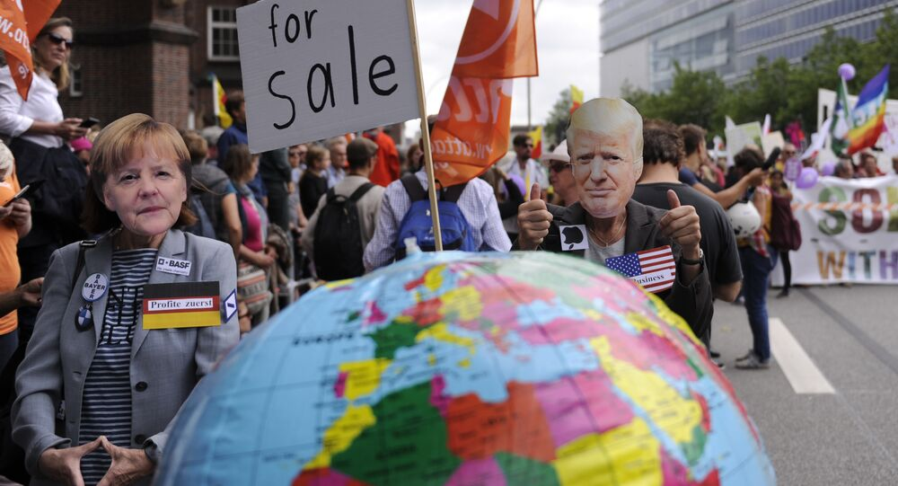 Protesters wear masks of German Chancellor Angela Merkel and US President Donald Trump as they take part in the solidarity without borders instead of G20 demonstration on July 8, 2017 in Hamburg, northern Germany as world leaders meet during the G20 summit