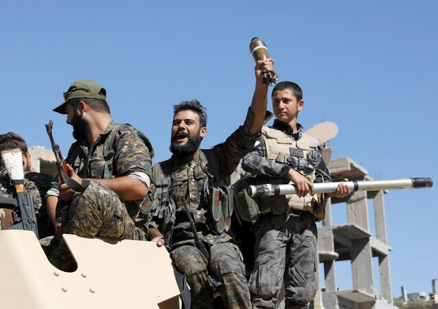 Fighters of Syrian Democratic Forces jubilate aboard an armoured fighting vehicle after Raqqa was liberated from the Islamic State militants, in Raqqa, Syria October 17, 2017