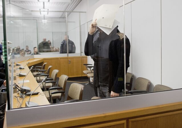 Abu Walaa covers his face while waiting at the High Regional Court of Celle, Germany, Tuesday, Sept.. 26, 2017. The 33-year-old Iraqi citizen and four fellow suspects are accused of membership in a terrorist organization, terror financing and public incitement to commit crimes. Abu Walaa, allegedly recruited young Muslims in Germany, and raised funds to send them to Syria and Iraq to join IS group
