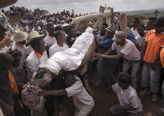 People carry a body wrapped in a sheet as they take part in a funerary tradition called the Famadihana in the village of Ambohijafy, a few kilometres from Antananarivo, on September 23, 2017