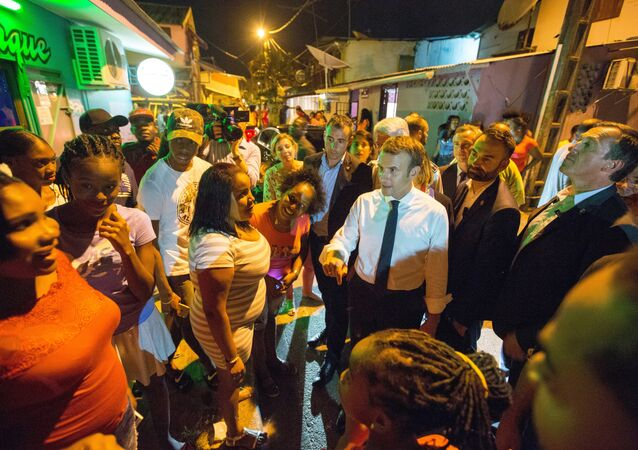 French President Emmanuel Macron (C,R) speaks with residents during a visit to the Crique neighborhood, in Cayenne, on October 27, 2017 as part of a three-day visit in French Guiana
